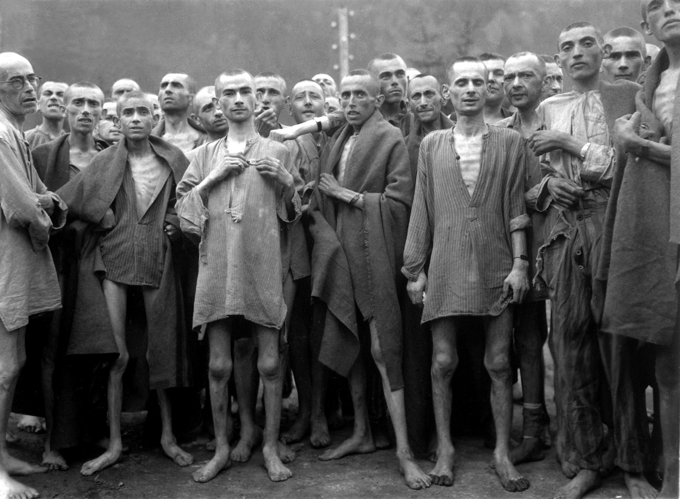 """Hladoví vězni, téměř mrtví od hladu, pózují v koncentračním táboře v Ebensee v Rakousku. Tábor byl údajně využíván pro """"vědecké"""" experimenty. Tábor byl osobozen 80. divizí. 7. května 1945. Poručík E. E. Samuelson."""